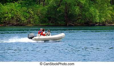 Boating on river - A couple driving an inflatable boat on a...