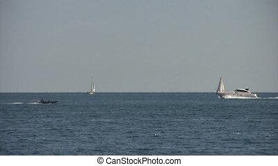 boating - speedboats pass sailboats on lake
