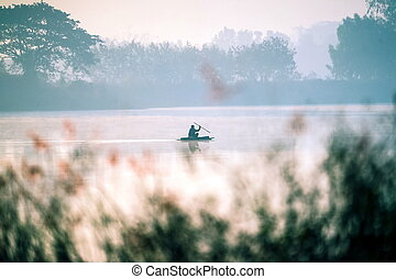 A lone boatman on the evening reservoir