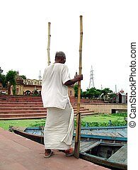 A traditional boatman approaching his boat in Lucknow India