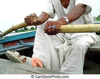 A traditional Indian boatman rowing his boat in river Gomti at Lucknow India
