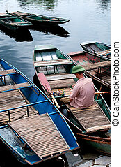 Boatman on a rowing boats waiting for customers