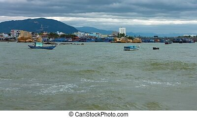 Small boats anchored off the rocky, urban, tropical coastline with buildings and traffic in the background, near Nha Trang, Vietnam. Video 4k