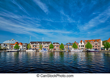 Boats and houses on Spaarne river. Haarlem, Netherlands - ...