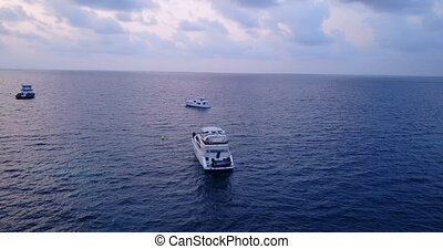 boats and sailing yachts with view from aerial flying drone in clear aqua blue sea water and blue sky
