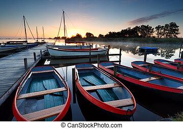boats and yachts on lake at sunrise