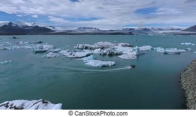 Boats are moving along the water near the glaciers and shores. Andreev.
