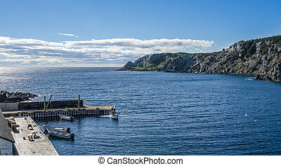 Boats at a cliff-side dock house in Twillingate, Newfoundland.