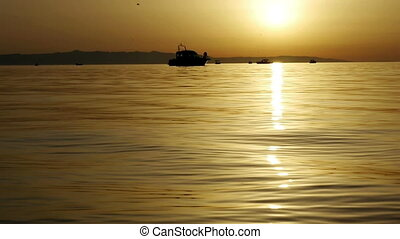 Boats at sea in golden sunset
