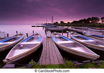 boats by pier on lake haven during sunrise