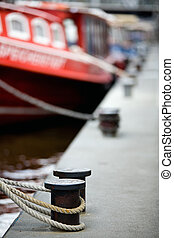 boats docked in harbor - tied to bollards - selective focus