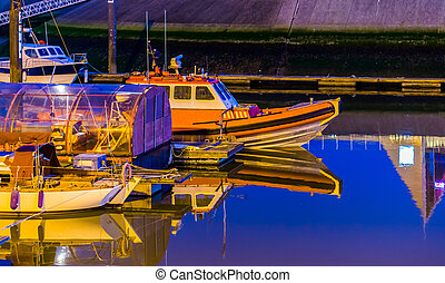 Boats docked in the harbor of Blankenberge at night, Belgium city architecture, water transportation