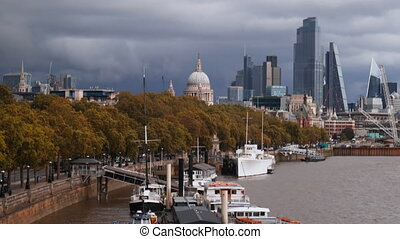 4k video of boats docked on the River Thames alongside a row of autumn-colored trees, with a cityscape, the Saint Paul Cathedral, and a heavily cloudy skyline as background