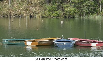 Boats Floating on Lake - Colorful wood boas tied togheter on...