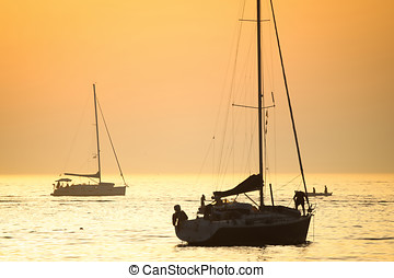 Boats in Adriatic sea at sunset - People on an anchored boat...