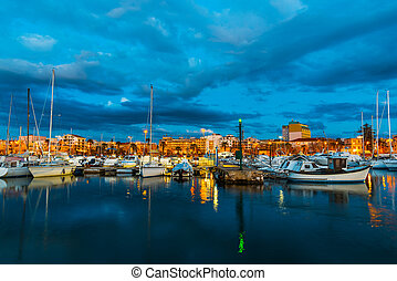 Boats in Alghero harbor at night