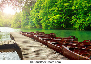 Boats in Plitvice lakes and pier, Croatia.