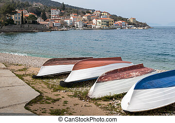 Boats lying on the beach of Valun on a cloudy day in spring