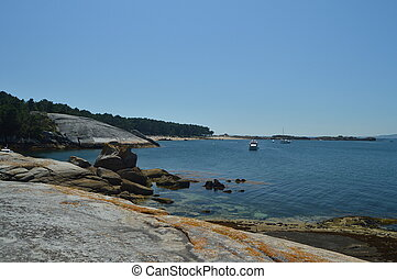 Boats Moored In The Estuary In Front Of The Horse Point Lighthouse On Arosa Island. Nature, Architecture, History, Travel. August 18, 2014. Isla De Arosa, Pontevedra, Galicia, Spain.