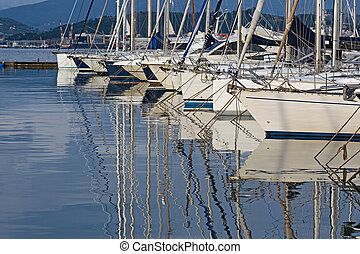 Boats moored in the harbour reflecting on the sea