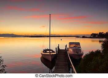 Boats moored to jetty at sunrise