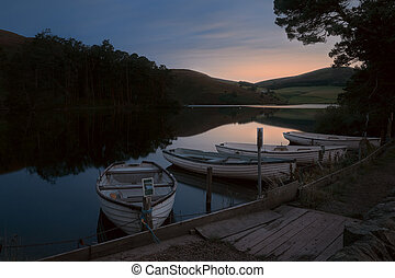 Boats moored to the shore of a night lake