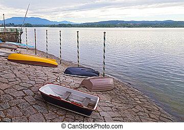 Boats on a lake shore at sunset