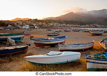boats on beach at sunset
