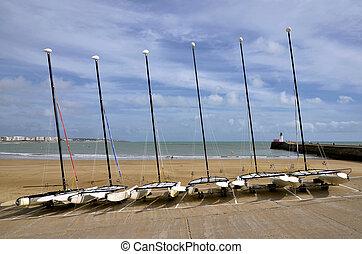 Little sailing catamarans on the beach of Les Sables d'Olonne, commune in the Vend?e department in the Pays de la Loire region in western France