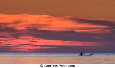 Boats on Horizon against Red Clouds in Dark Sky after Sunset