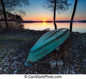 Boats on lake shore at sunset