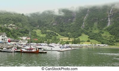 Boats on moorage of coastal village and camping under mountain