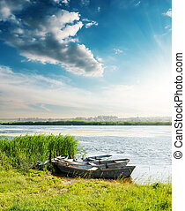 boats on river in sunset and blue sky with clouds