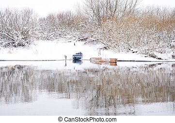 Boats on shore of winter river
