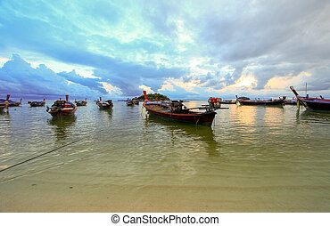 Boats on shore with sunset background, Thailand