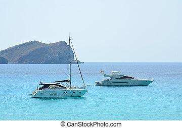 Boats floating on the Balearic sea by Ibiza island, Spain.