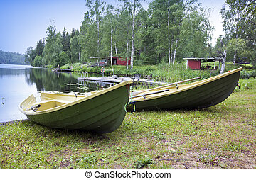 Boats on the bank of the forest lake