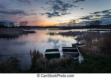 Boats on the shore of a quiet lake, view after sunset