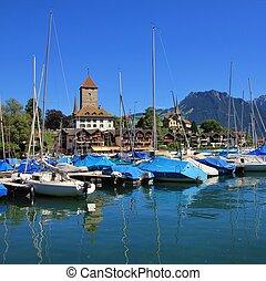 Boats on the shore of Lake Thun. Schloss Spiez, Bernese Oberland. Switzerland.