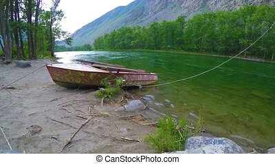 Boats on the shore of the taiga river in the foothills of...