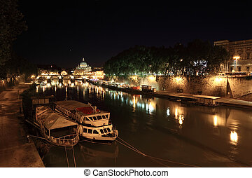 Boats on Tiber river, Sant' Angelo Bridge and Basilica of St. Peter at night in Rome, Italy