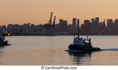 Boats pass in the bay near city waterfront in beautiful warm lighting