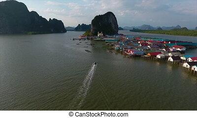 Boats sailing back to a settlement - An establishing shot of...