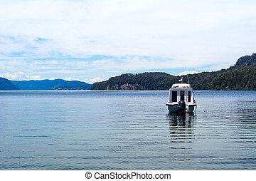 Boats sailing on calm lake water.