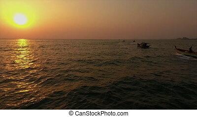 Boats sailing towards an evening sun - A medium shot of...