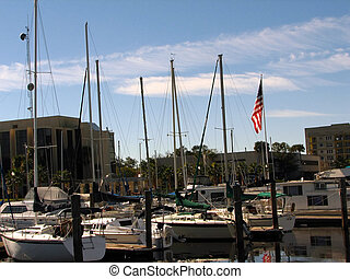 Shot of several boats at the pier in Sanford, Florida. As a background we can see a few buildings, palm trees, trees and an American Flag.