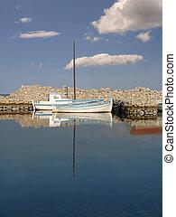 White boat anchored on calm sea