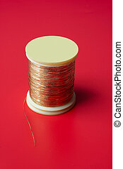 bobbin of golden thread on a red background