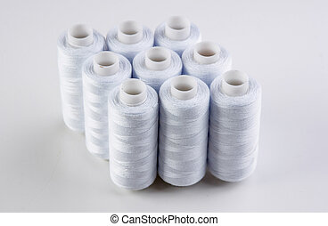 bobbin with white thread on a white background