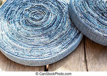 Bobbins of jeans cotton ribbon laying on the wooden plank or plate